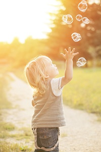 child catching bubbles
